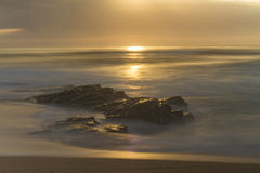 Sun Rising over a Rocky Beach Stock Images