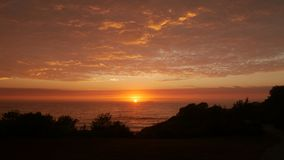 Sunrise over the ocean on the coast. The sun rising over the Tasman Sea just off Caves Beach in New South Wales. The sky is illuminated in a golden orange and Royalty Free Stock Images