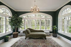 Sun room in luxury home. Sunroom in luxury home with sofa and wall of windows royalty free stock photos