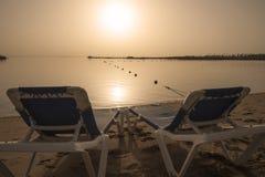 Sun-Ruhesessel auf tropischem Strand bei Sonnenaufgang Stockfotos