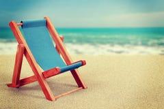 Sun-Ruhesessel in der Weinlese des sandigen Strandes getont Lizenzfreies Stockfoto