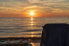 Sun-Ruhesessel durch das Meer während des Sonnenuntergangs stockfotografie
