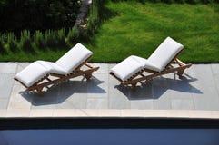 Sun-Ruhesessel durch einen Swimmingpool Lizenzfreies Stockfoto