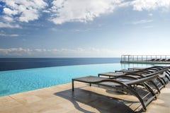 Sun-Ruhesessel durch einen UnendlichkeitsSwimmingpool Stockfoto