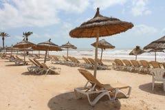 Sun-Ruhesessel mit Regenschirmen auf dem Seeufer Lizenzfreies Stockbild