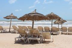 Sun-Ruhesessel mit Regenschirmen auf dem Seeufer Stockfoto