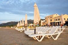 Sun-Ruhesessel und -regenschirme auf dem Strand Stockfoto