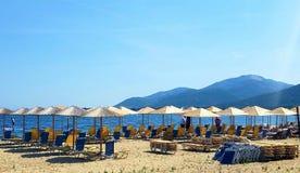 Sun-Ruhesessel und -regenschirme, die auf Feiertagshersteller auf einem Strand in Griechenland warten lizenzfreie stockfotografie