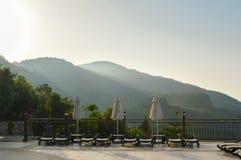 Sun-Ruhesessel und -sonnenschirme gegen den Hintergrund der Berge früh morgens Lizenzfreie Stockfotografie