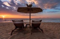 Sun-Ruhesessel unter Regenschirm auf Sand Lizenzfreie Stockfotografie