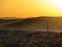 Sun-Sätze über Stadt im Tal stockbilder