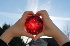 The Sun's Heartbeat. Young girl holding a red crystal ball towards the sun that it glows like a heart Royalty Free Stock Image