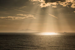 The sun's rays on boats over the island of Elba Stock Photo