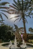 Dolphin fountain with sunlight rays coming through palm trees. The sun`s rays break through palm trees to light a dolphin fountain Royalty Free Stock Photo