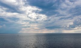 The sun`s rays through the clouds illuminate the sea. royalty free stock image