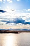 The sun's rays in clouds, water and mountain Royalty Free Stock Images