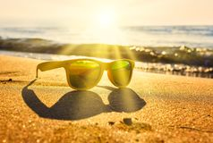 Sun`s rays cut through the stylish yellow sunglasses on the edge of the shore near the waves on sand. stock image