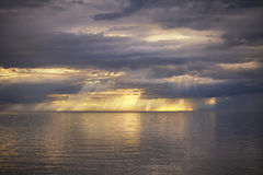 The sun's rays and the light breaking through the clouds over th. E sea. On the surface of the sea a colorful reflection of the sky Royalty Free Stock Photos