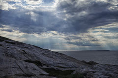 The sun`s rays make their way through the clouds over the sea and the rock. After the storm Royalty Free Stock Photography