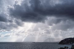 The sun`s rays over the sea in the cloudy sky stock images