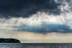 The sun's rays passing through the storm clouds over the sea Royalty Free Stock Photo