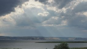 The sun`s rays penetrate the dark storm clouds.  stock video footage