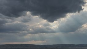 The sun`s rays penetrate the dark storm clouds.  stock video