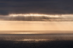 The sun's rays pierce the clouds and fall to the Atlantic Ocean, stretching to the horizon Stock Photo