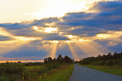 The sun's rays on a rural field in the sunset.  Stock Photography