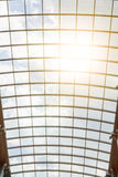 The sun`s rays shine through the glass roof of the shopping center. Beautiful modern architectural background. Blue cloudy sky and Stock Image