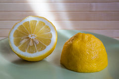 The sun's rays shine on half a lemon. On a green plate Stock Photography