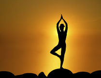 Sun Salutation 3. Silhouette of woman in standing yoga pose with sunrise in the background Stock Photos