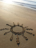 Sun in the sand. A sun drawned in the sand of a beach stock photography