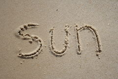 Sun in the sand. Sun written on the beach Stock Photos
