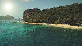 Sun sand beach at green mountain island with passenger boats, rest travelers aerial panorama view