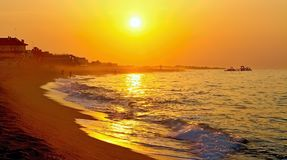 The rays of the rising sun over the Mediterranean Sea with a muddy background in Malgrat de Mar, Spain. Sun and sand, Mediterranean sea with sea waves, Sunrise Royalty Free Stock Photos