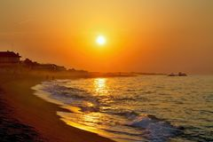 The rays of the rising sun over the Mediterranean Sea with a muddy background in Malgrat de Mar, Spain. Sun and sand, Mediterranean sea with sea waves, Sunrise Royalty Free Stock Images