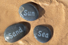 Sun Sand and Sea pebbles on the beach Stock Images
