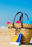 Sun screen on the beach. Various  bottles of sun screen and a modern bag filled with slippers and a towel Royalty Free Stock Photo