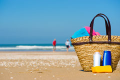 Sun screen on the beach. A basket with a towel, slippers and bottles of sun screen in the foreground on a beach. A happy couple in the background (blurred Stock Photos