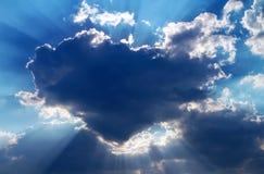 Sun se cachant derrière un nuage sous forme de coeur Photos stock
