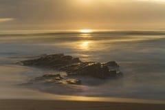 Sun se levant au-dessus de Rocky Beach Images stock