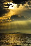Sun Sea Mountain. Shot of a sun in late afternoon behind the clouds and with reflection on the sea royalty free stock image