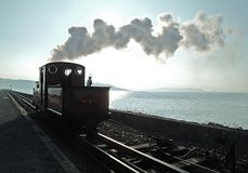 Sun sea steam shadow. An against the light (contre jour) shot of steam from an old narrow gauge locomotive drifting across the sun with sea and hills in royalty free stock photo