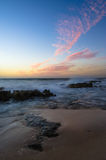 Sun set. At the beach with rocks on the foreground Royalty Free Stock Photography