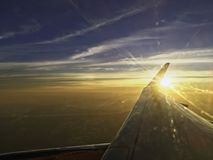 Sun set on horizon cloud sky  through airplane wing. With land and ocean down below in background Stock Photo