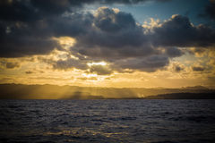 Sun Set over island mountains from the ocean Royalty Free Stock Image