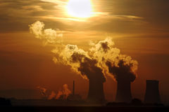 Sun set over smoking nuclear power plant Royalty Free Stock Image