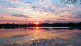 Sun set reflecting in calm lake Royalty Free Stock Image