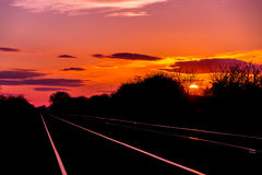 Sun set rise at railway tracks. Sun set or rise near railway tracks with orange background and clouds Royalty Free Stock Photography